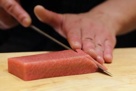 46691638 - hand of japanses sushi chef slice a fresh raw sashimi